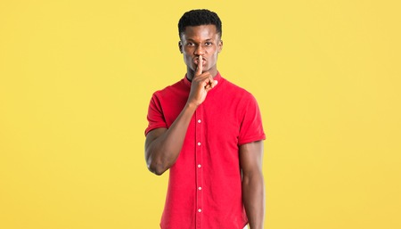 Young african american man showing a sign of closing mouth and silence gesture putting finger in mouth on yellow background