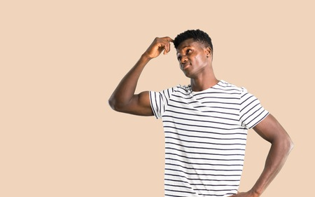 Dark skinned man with striped shirt having doubts and with confuse face expression while scratching head on isolated ocher background Stock Photo