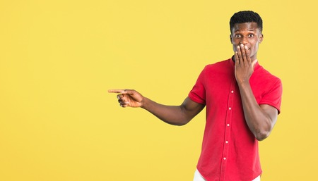Young african american man pointing finger to the side and presenting a product with a surprised face while covering mouth on yellow background Imagens