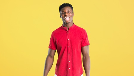 Young african american man showing tongue at the camera having funny look on yellow background