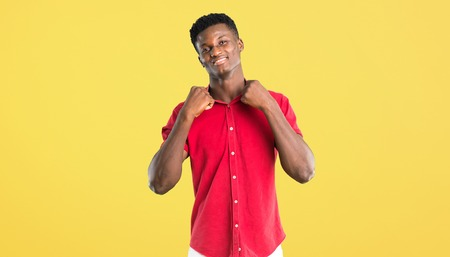 Young african american man proud and self-satisfied in love yourself concept on yellow background