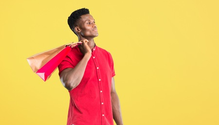 Young african american man holding a lot of shopping bags on yellow background