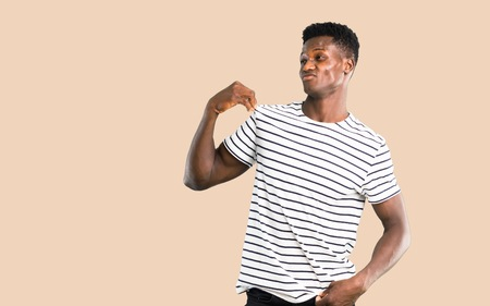 Dark skinned man with striped shirt proud and self-satisfied in love yourself concept on isolated ocher background Stock Photo