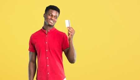 Young african american man holding a credit card and thinking on yellow background