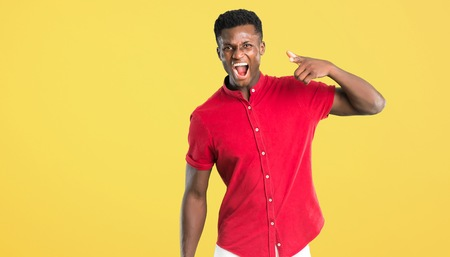 Young african american man annoyed angry in furious gesture. Frustrated by a bad situation and pointing to the front on yellow background