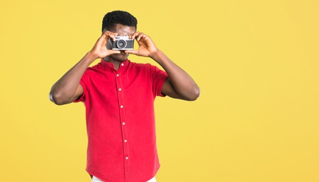Young african american man holding a camera and photographing something on yellow background Imagens