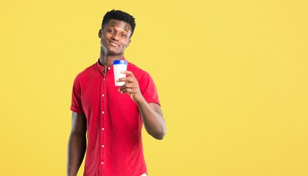 Young african american man holding hot coffee in takeaway paper cup on yellow background
