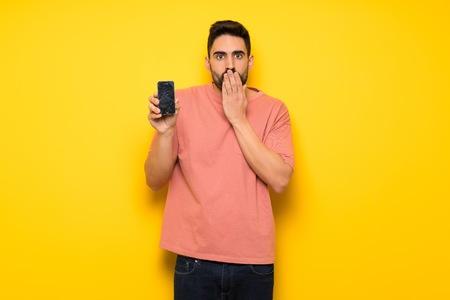 Handsome man over yellow wall with troubled holding broken smartphone Stock Photo
