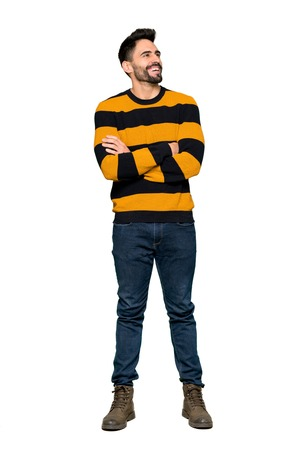Full-length shot of Handsome man with striped sweater keeping the arms crossed while smiling on isolated white background