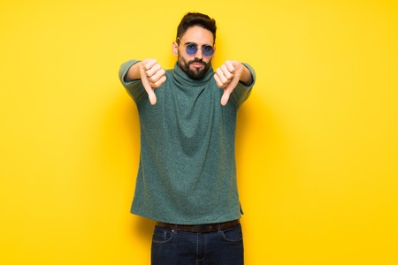 Handsome man with sunglasses showing thumb down with both hands