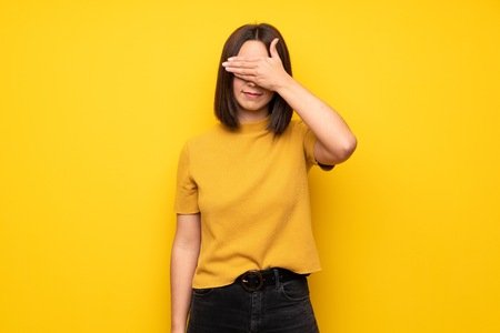 Young woman over yellow wall covering eyes by hands. Do not want to see something