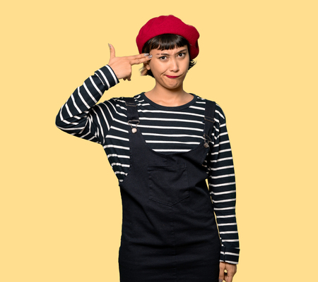 Young woman with beret with problems making gun gesture over yellow background