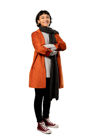 A full-length shot of a Short hair woman with coat with arms crossed and looking forward over isolated white background