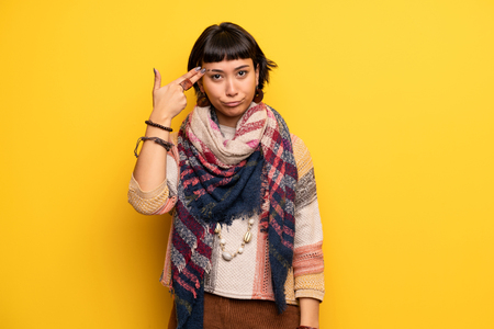 Young hippie woman over yellow wall with problems making gun gesture Banco de Imagens