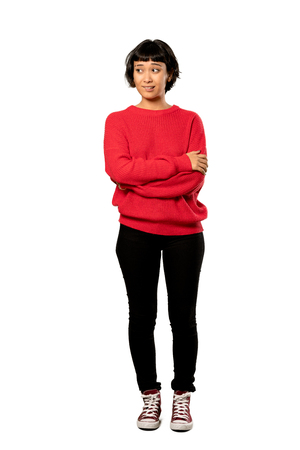 A full-length shot of a Short hair girl with red sweater with confuse face expression while bites lip over isolated white background