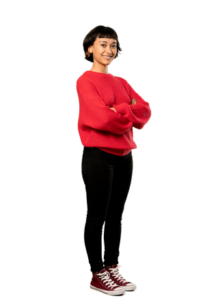 A full-length shot of a Short hair girl with red sweater with arms crossed and looking forward over isolated white background