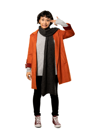 A full-length shot of a Short hair woman with coat with problems making gun gesture over isolated white background