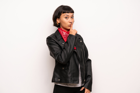 Woman with leather jacket and handkerchief showing a sign of silence gesture putting finger in mouth