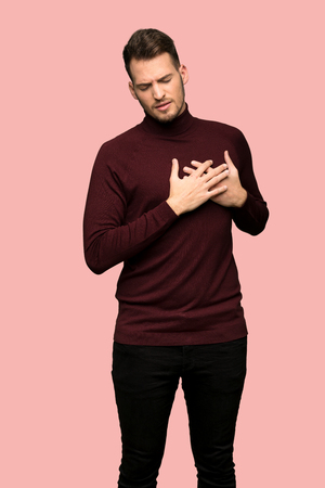 Man with turtleneck sweater having a pain in the heart over pink background
