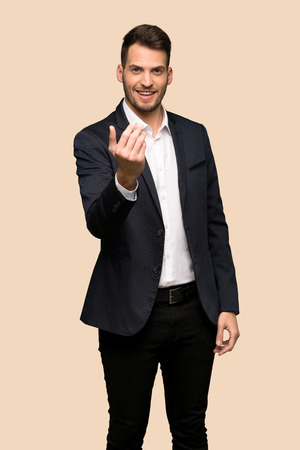 Handsome business man inviting to come with hand. Happy that you came over ocher background