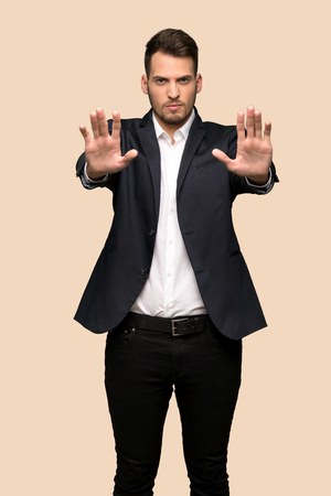 Handsome business man making stop gesture and disappointed over ocher background Reklamní fotografie