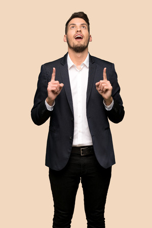 Handsome business man surprised and pointing up over ocher background