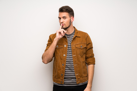 Handsome man over white wall showing a sign of silence gesture putting finger in mouth