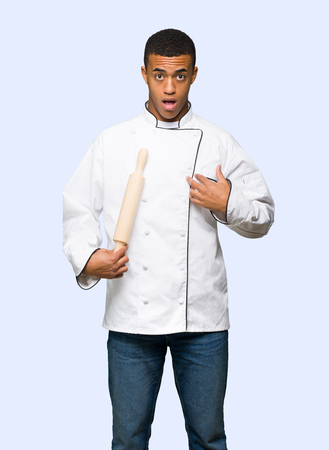 Young afro american chef man surprised and shocked while looking right on isolated background Banque d'images