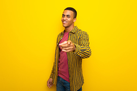 Young afro american man on yellow background points finger at you with a confident expression Imagens