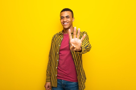 Young afro american man on yellow background happy and counting four with fingers Imagens