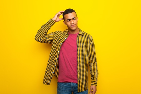 Young afro american man on yellow background having doubts while scratching head Stock Photo