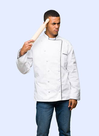 Young afro american chef man making the gesture of madness putting finger on the head on isolated background