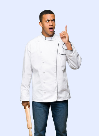 Young afro american chef man thinking an idea pointing the finger up on isolated background Stock Photo