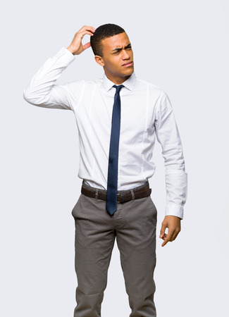 Young afro american businessman having doubts while scratching head on isolated background Stock Photo