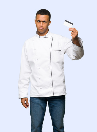 Young afro american chef man taking a credit card without money on isolated background Archivio Fotografico