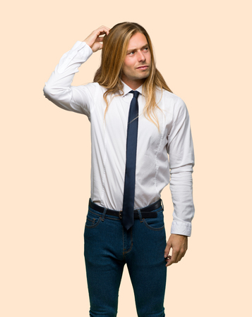 Blond businessman with long hair having doubts while scratching head on isolated background Foto de archivo