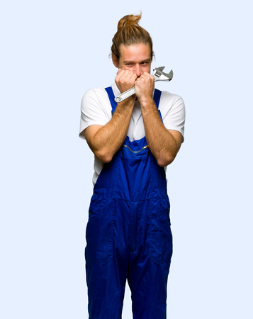 Workman is a little bit nervous and scared putting hands to mouth on isolated background