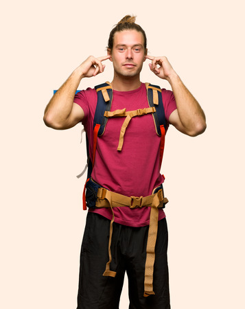 Hiker man with mountain backpacker covering both ears with hands on isolated background