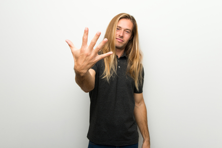 Blond man with long hair over white wall counting five with fingers Stock Photo