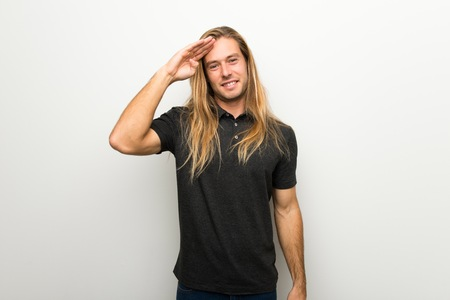 Blond man with long hair over white wall saluting with hand