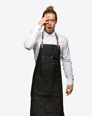 Barber man in an apron with surprise and shocked facial expression on isolated background