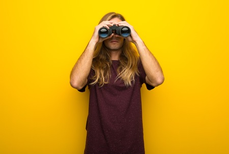 Blond man with long hair over yellow wall and looking in the distance with binoculars