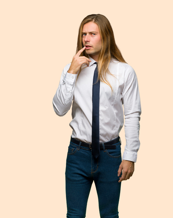 Blond businessman with long hair having doubts while looking up on isolated background