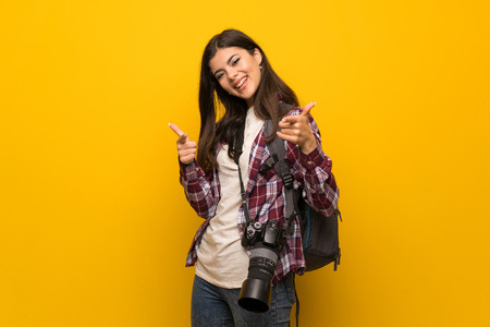 Photographer teenager girl over yellow wall pointing to the front and smiling