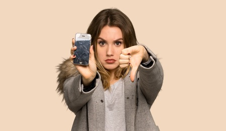 Teenager girl with coat with a broken phone on isolated yellow background