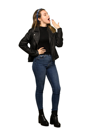 A full-length shot of a Teenager girl with leather jacket yawning and covering wide open mouth with hand on isolated white background