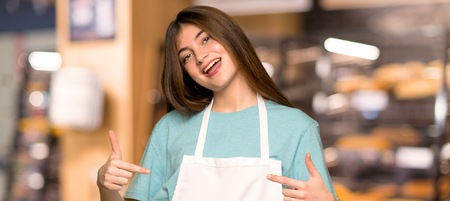 Girl with apron proud and self-satisfied in love yourself concept in a bakery
