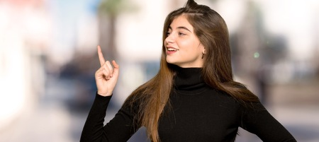 Pretty girl showing and lifting a finger in sign of the best at outdoors