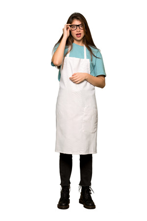 Full-length shot of Girl with apron with glasses and surprised on isolated white background