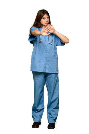 Full-length shot of Young nurse is a little bit nervous and scared stretching hands to the front on isolated white background